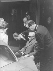 The Duke of Windsor being assisted to get on the automobile while he's sitting on the wheelchair.