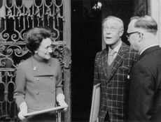 The Duke and Duchess of Windsor in a conversation with a man.