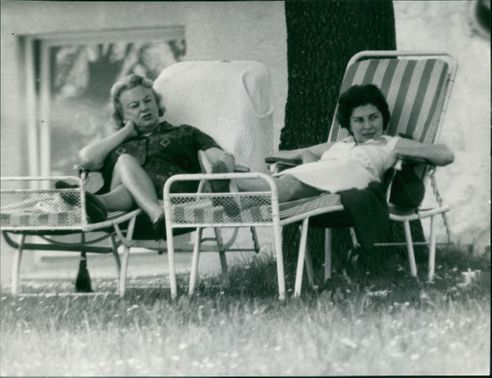 Princess Soraya of Iran, sitting on a bench with a woman, looking somewhere.