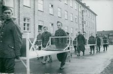Prisoners carrying steel bed frames outdoor in Germany.  - 1939