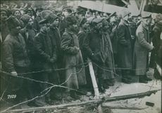 Soldiers standing together in street and looking at something. 1936