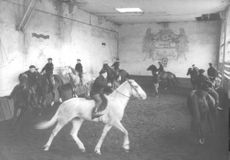People riding horse indoor.