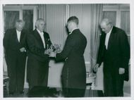 The popular outgoing janitor Adolf Eriksson receives the silver takers from the hand of the other trustee.