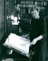 Mrs Marcilhacy, wife of Pierre Marcilhacy turning the pages of a book.