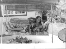 Marina Vlady relaxing on swing with a man.