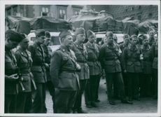 Soldiers gathered in street and looking at something or someone.