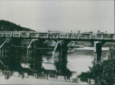 View of a bridge over river, carriers moving over it.
