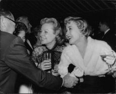 June Allyson having a good laugh and drink in a party.  - 1955