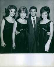 Man posing with three women.