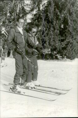 Roger Moore takes a ski lift together with his ski instructor