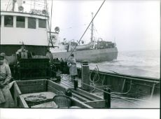 Men standing and operating the boat.