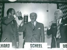 Walter Scheel having a toast together with two other men in Munich. November 1972