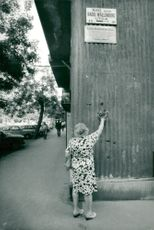 A woman commemorates Raoul Wallenberg by the street carrying his name. The city is unknown.