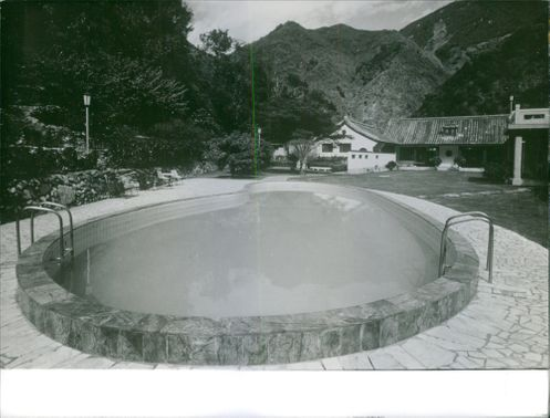 A view of a swimming pool surrounded by mountain.