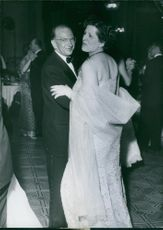 Edgar Faure smiles while dancing with Mme Georges Bidault.