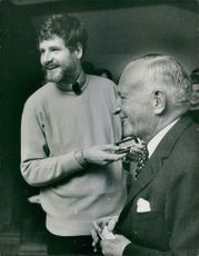 Two men looking at something and laughing.