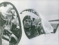 A photo of  a Soviet test pilot, aerospace engineer and cosmonaut in the first group of cosmonauts selected in 1960, Vladimir Mikhaylovich Komarov sitting in the aircraft, preparing to fly.