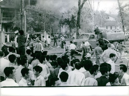 A building is on fire, some people help to stop the fire, people watching around, in Saigon, Vietnam, January 1965.