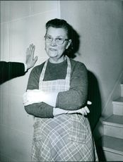 1964 Paris Woman wearing apron and gloves facing camera and smiling .