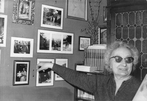 Woman pointing Pope Paul VI picture on the wall.