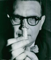 A man on specs holding an ampule.