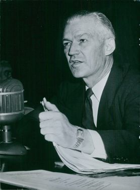 Close-up photo of an American personality: Rosel H. Hyde, sitting on his desk, holding papers while talking to someone.