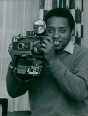 José Germano de Sales holding a camera.  Better known only as Germano with the Brazilian Olympic National took part in the Pan American Games in 1959 and qualifying for the Olympics in 1960 .