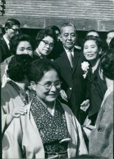 Eisaku Sato standing with women.