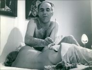 Michel Piccoli playing with a snake on the body of a woman.