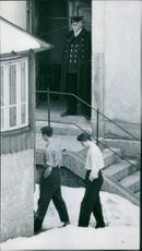 An officer is standing at the entrance of a building and two men are walking through the road.1956  Punishment Scandal