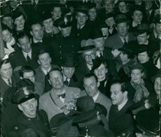 Maurice Chevalier surrounded by among people.