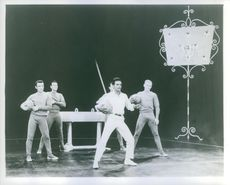 Johnny Mathis performing in stage with a group of artist, both of them hold a basketball