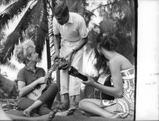 Roger Vadim with friends holding musical instrument.