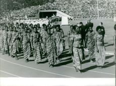 Tribal people parading in the track field, stadium full of audience, October 1964.