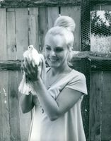 Marie-France Boyer holding a pigeon and she's smiling.