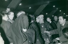 Group of men, one with gun in his pocket.