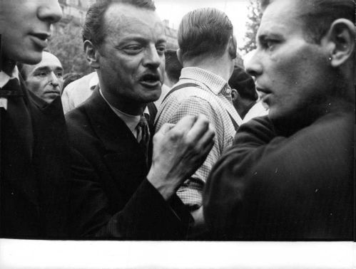 Men talking while in a crowd during the Algerian War.