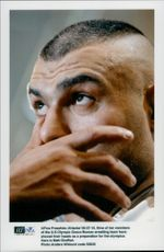 Wrecker Matt Ghaffari with shaved head in front of the 1996 Olympic Games