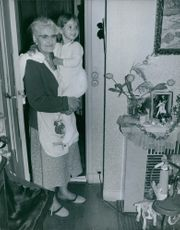 Regine Rumen's mother  carrying her daughter and smiling. Photo taken on October 6, 1965.