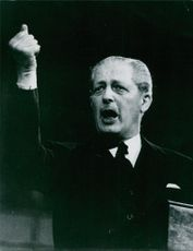 A photo of a British Conservative politician and statesman who served as the Prime Minister of the United Kingdom from 10 January 1957 to 18 October 1963 Maurice Harold Macmillan delivering aggressive speech.