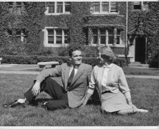 A man and a woman looking and smiling at each other while sitting on a grassy field.