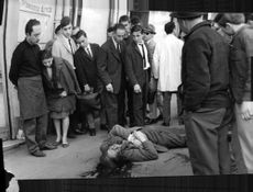 People are standing and looking at the bloody dead man lying on the street during Algerian war.