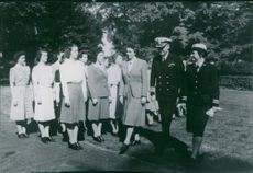 Colonel Mildred Mcafee with the other officers walking, while group of women standing in attention position.