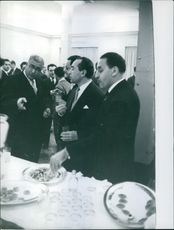 Ferhat Abbas is eating whiler talking to his colleagues. 1954