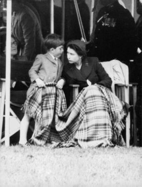Princess Alexandra with her son James wisphering while watching a game outdoors