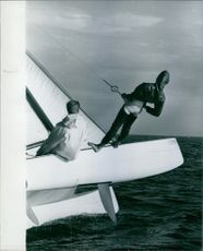 A man on the boat with a protective gear about to go down to the sea, 1965.