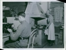Soldier working on typewriter and his wife working in kitchen.