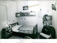 A view of a room. There is a bookshelf, a hat, a bed and etc.