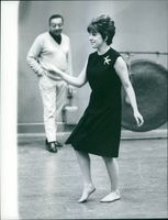 Carol Sloane in shoeless is dancing while being watched by a man.