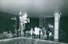 A man about to dive into the swimming pool.